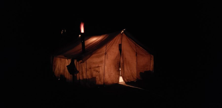 Wall tent glowing at night.